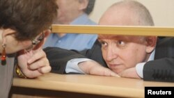 Vladimir Kozlov looks out from a glass-walled cell during his trial in the city of Aqtau last month.
