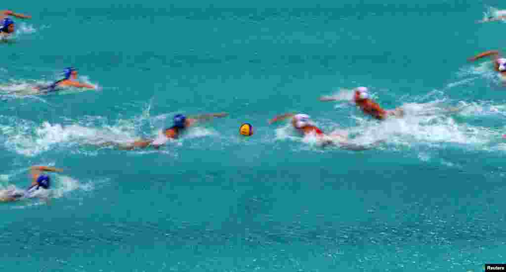 Spanish and Hungarian players start their preliminary-round water polo match.