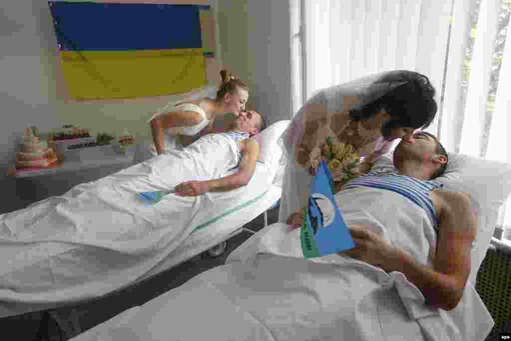 Wounded Ukrainian paratroopers Ruslan Yarish (right) and Oleksandr Ponomaryov kiss their brides during their wedding in the central military hospital in Kyiv, on July 9. (epa/Maksim Marusenko)