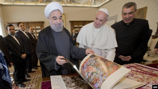 Pope Francis (center right) and Iranian President Hassan Rohani (center left) exchange gifts during their private audience at the Vatican on January 26.