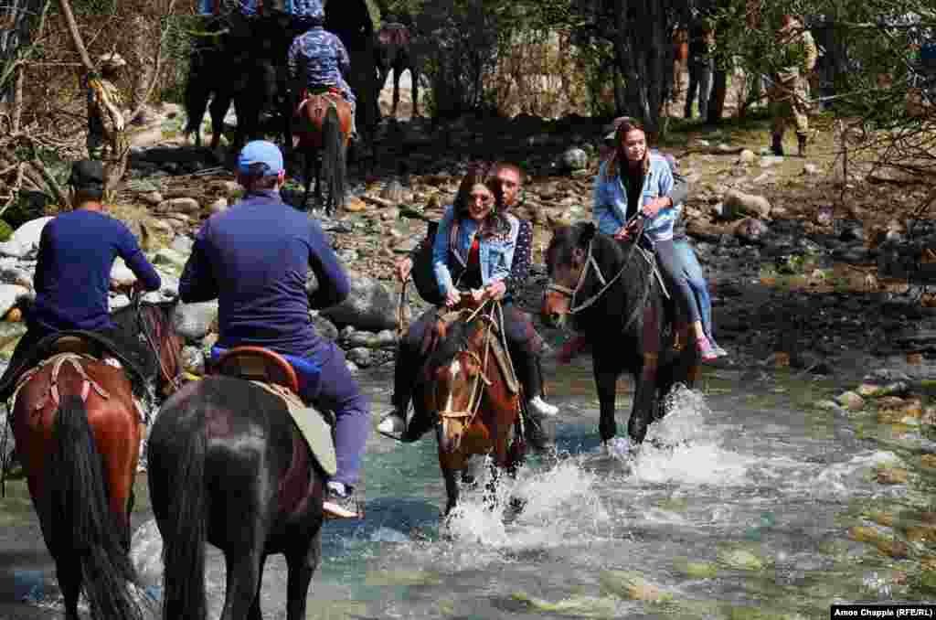"Friends splash through a swift mountain stream on their way to the games. These Nomad Games' slogan was ""United in Strength! United in Spirit!"""