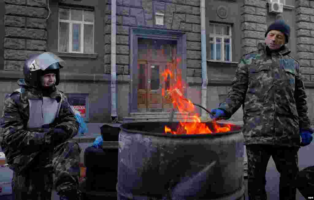 Maidan veterans warm themselves while guarding the entrance to the Presidential Palace near Independence Square.