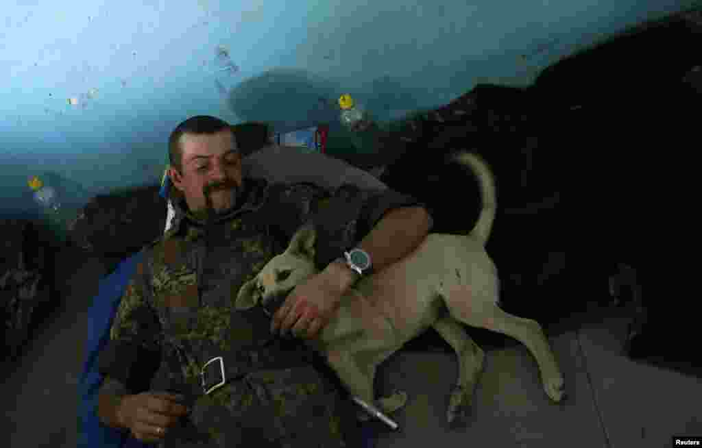 A Ukrainian serviceman rests with a dog at a military camp near the town of Horlivka in eastern Ukraine in September 2014.
