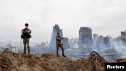 Сотрудники сил безопасности на месте взрыва в порту Бейрута. 6 августа 2020 года.