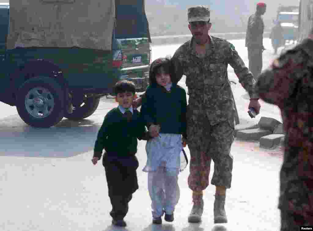 A soldier escorts schoolchildren after they were rescued from the Army Public School.