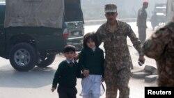პაკისტანის ჯარისკაცს შემთხვევის ადგილიდან მიჰყავს გადარჩენილი სკოლის მოსწავლეები