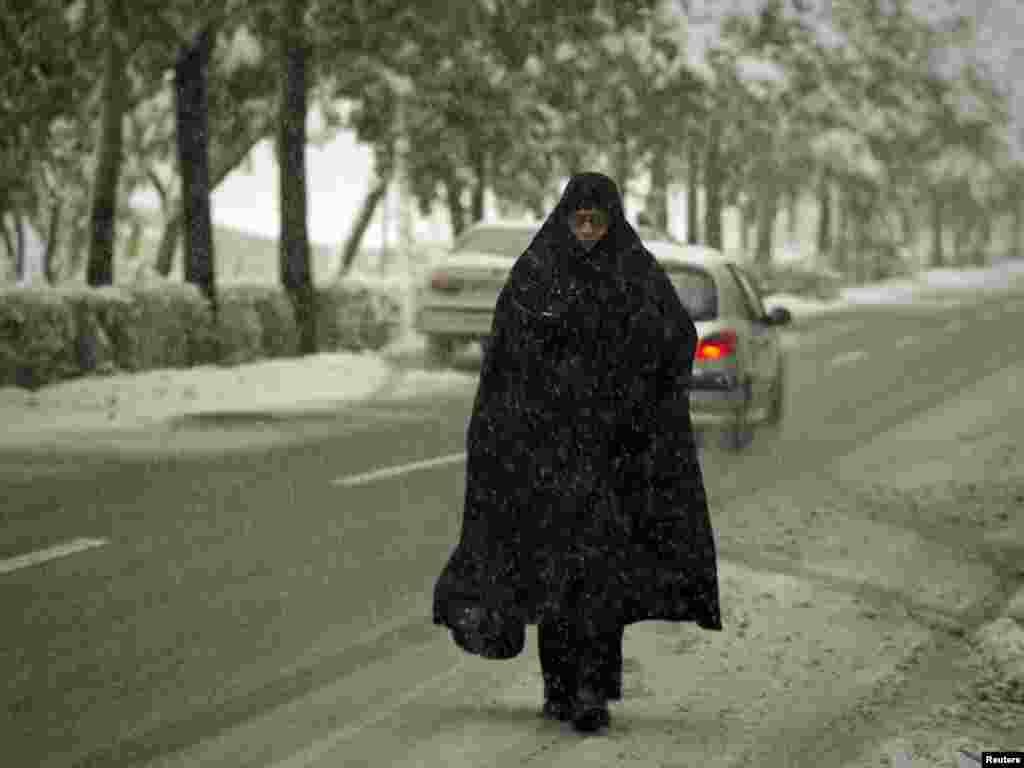 A woman walks on a street during a rare autumn snowstorm in Tehran. (Photo for Reuters by Caren Firouz)