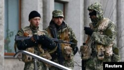 Pro-Russian gunmen stand guard outside the mayor's office in Slovyansk, Ukraine, on April 14. Can Kyiv prove some are Russian servicemen?