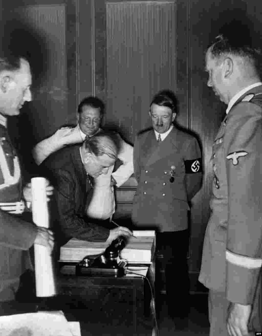 French Prime Minister Daladier signs the Munich Agreement as Hitler (second right), Reichsmarshal Hermann Goering (third left), Hitler's secretary Martin Bormann (right), and top Nazi officers look on. France refused to fight Germany alone and followed the British lead, despite a military pact with Czechoslovakia.