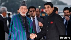 Afghan President Hamid Karzai (left) shakes hands with Indian Minister of State for Home Affairs R.P.N Singh on his arrival in New Delhi on December 12.