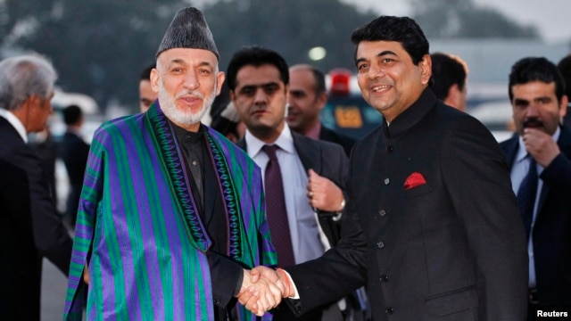 Afghan President Hamid Karzai (left) shakes hands with Indian Minister of State for Home Affairs R.P.N Singh upon his arrival at the airport in New Delhi on December 12.