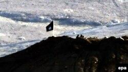 پرچم سیاه گروه موسوم به «دولت اسلامی» و نیروهای این گروه بالای تپهای در خاک سوریه