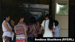 """Жители комплексов """"Махаббат"""" стоят у входа в здание """"Казпочты"""". Астана, 3 июля 2015 года."""
