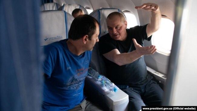 Володимир Балух та Едем Бекіров у літаку під час повернення до Києва в рамках обміну утримуваними особами між Україною і Росією 7 вересня 2019 року