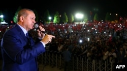 Turkish President Recep Tayyip Erdogan addresses people gathered at the Presidential Complex to protest the July 15th failed military coup attempt in Ankara, on August 10.