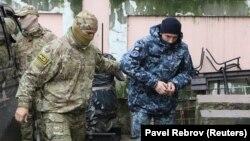 Працівник російської ФСБ веде українського моряка в будівлю підконтрольного Кремлю суду в Сімферополі, 27 листопада 2018 року
