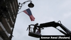 A worker hangs a U.S. flag on a lamppost along a street where the U.S. Consulate in located in Jerusalem.