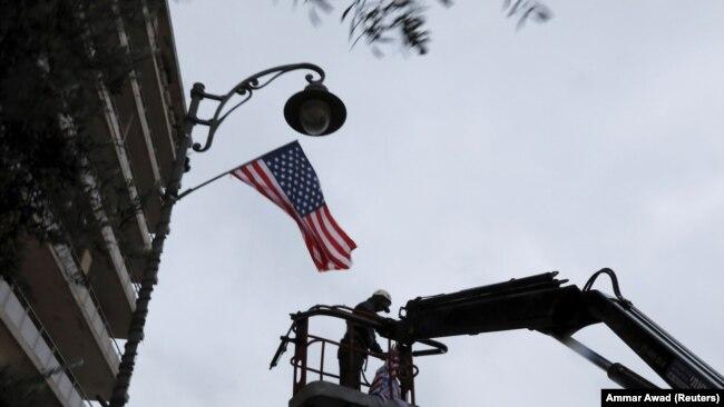 Izrael: Një punëtor vendos flamurin amerikan në një shtyllë që gjendet në rrugën ku ndodhet konsullata e SHBA-së në Jerusalem. 6 dhjetor, 2017