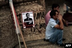 Protesters sit near a poster portraying Prime Minister Recep Tayyip Erdogan as Hitler in Istanbul on June 5.