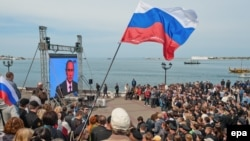 Crimean residents watch a TV broadcast with Russian President Vladimir Putin after the peninsula was annexed by Moscow earlier this year.