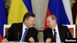 Президент Украины Виктор Янукович (слева) подмигивает президенту России Владимиру Путину во время встречи в Кремле. Москва, 17 декабря 2013 года.