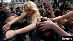 Ukrainian activist Inna Shevchenko (center) and other members of the women's rights group Femen struggle with police officers during a protest in Paris in April 2013.