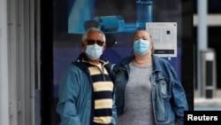 Люди в защитных масках на автобусной остановке в Лондоне. 10 июня 2020 года.