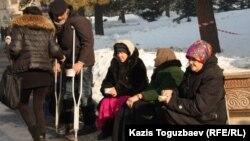 Девушка раздает милостыню у церкви. Алматы, 7 января 2013 года. Иллюстративное фото.