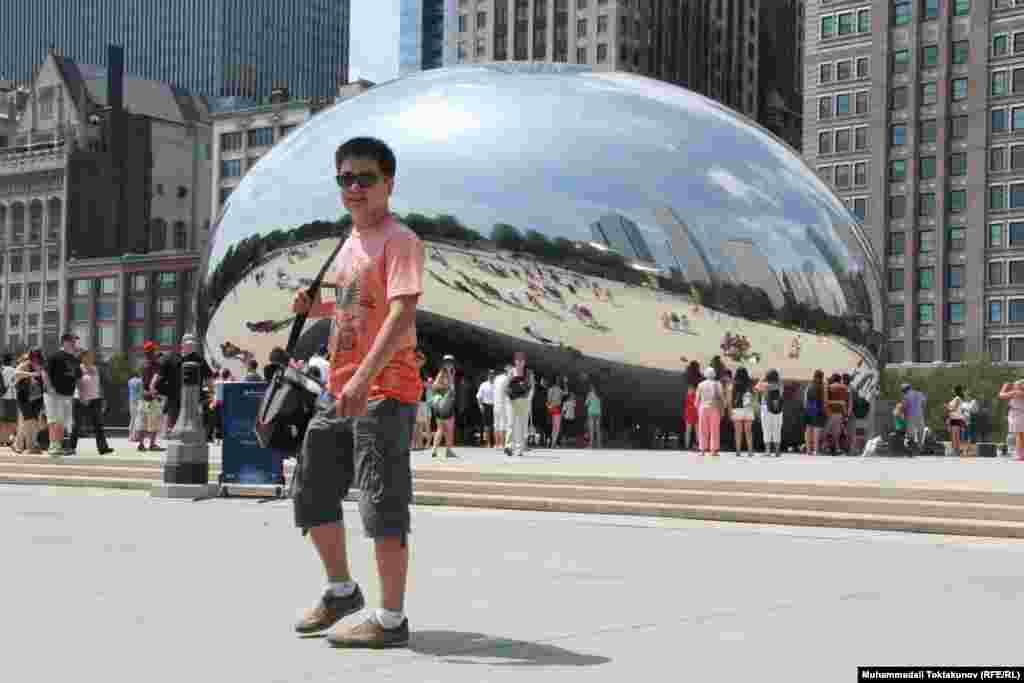 """Телеведущий программы """"Азаттык+"""" Али Токтакунов на фоне уникальной зеркальнойскульптуры """"Облачные врата"""" - абстрактного образа фасолевого зерна, Чикаго, 29 июля 2012 года."""