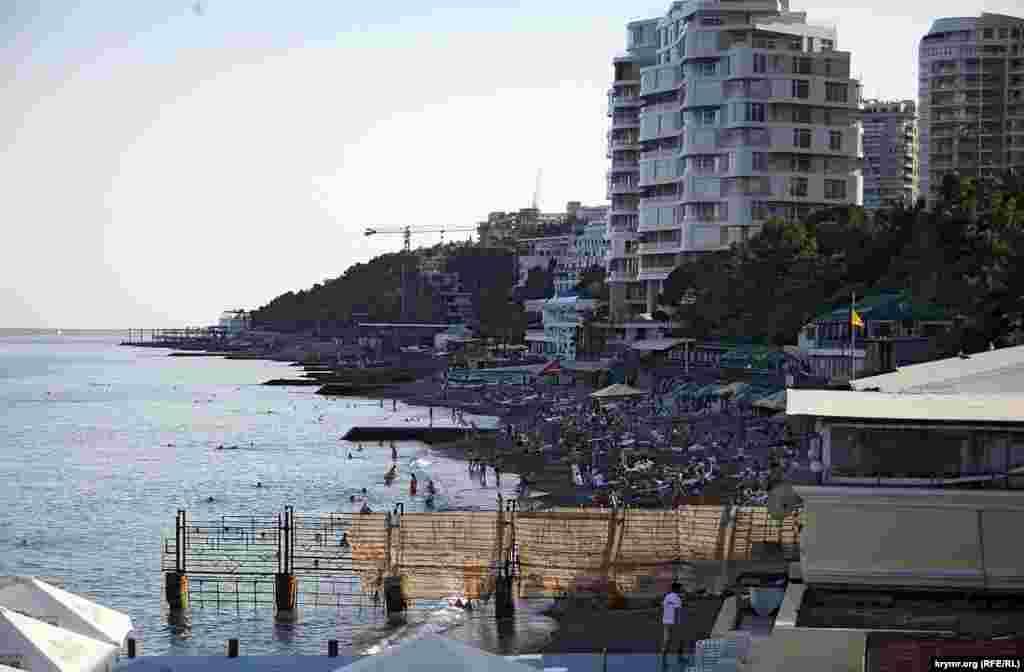 Міський пляж у Приморському парку, навпроти легендарного готелю «Ореанда». Люди є, тож удень цей пляж, очевидно, заповнений. Щоправда, міським є лише ближня частина пляжу, наступні карти пляжів розхапали новоявлені забудовники, а далі починаються володіння курортного монстра – санаторію «Росія», колишньої власності ЦК КПРС. Іржавим парканом з накинутою на нього рваною маскувальною сіткою убезпечує свій пляж від міського дирекція готелю «Ореанда» (пляж готелю на фотографії внизу).