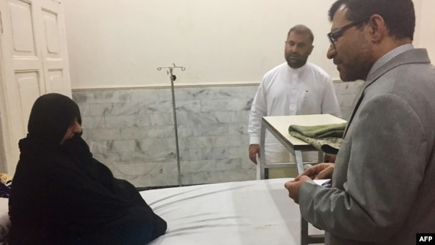 Afghan Consul-General Abdul Waheed Poyan (right) talks with Sharbat Gula in a hospital in Peshawar on November 2.