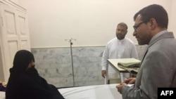 Представитель генконсульства Афганистана Абдул Вахид Поян (справа) беседует с Шарбат Гулой в пешаварском госпитале. 2 ноября 2016 года.
