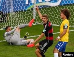 Футболист сборной Германии Томас Мюллер (в центре) после того, как забил гол в ворота бразильской команды. 8 июля 2014 года.