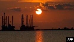Нефтедобывающие конструкции на фоне заката солнца, штат Луизиана, США