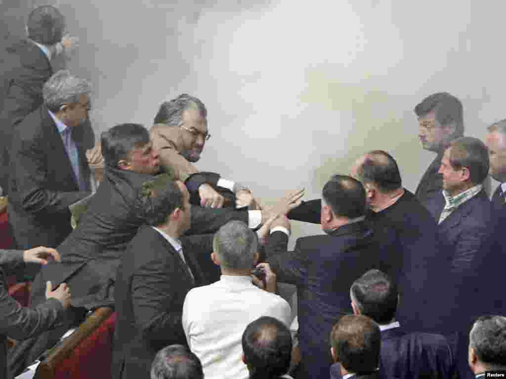 Deputies scuffle during a session of the Ukrainian parliament in Kyiv on April 27. Opposition lawmakers hurled eggs and smoke bombs inside the chamber as lawmakers approved an agreement allowing Russia's Black Sea Fleet to stay at Sevastopol until 2042. Photo by Gleb Garanich for Reuters