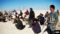 Afghans await remarks by the governor of Helmand Province, Muhammad Naeem Baloch, near the location of the rocket attack on January 1.