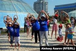 Женщины и дети принимают участие в коллективной физической зарядке. Алматы, 23 июня 2012 года.