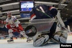 Алексей Калюжный из сборной Беларуси (слева) забивает гол в ворота сборной США на чемпионате мира по хоккею. Острава, 7 мая 2015 года.
