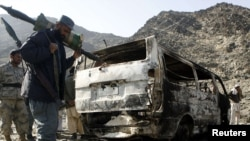 A border policeman stands next to burnt vehicles belonging to a team of Afghan deminers who were kiddnapped by the Taliban in Momand Dara.