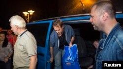 Первая группа наблюдателей ОБСЕ выходит из машины в Донецке после своего освобождения, рядом стоит самопровозглашенный премьер так называемой Донецкой народной республики Александр Бородай (справа). 26 июня 2014 года.