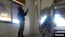UN chemical weapons experts, wearing gas masks, inspect one of the sites of an alleged chemical weapons attack in a Damascus suburb earlier this year.