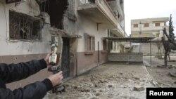 یک شهروند سوری بازمانده خمپاره های پرتاب شده به سور شهر حمص از سوی ارتش سوریه را نشان می دهد.