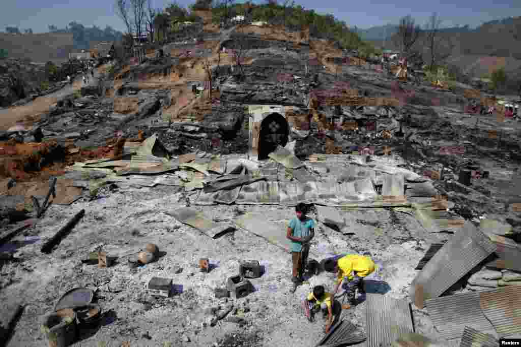 Refugee boys from Myanmar look for items to salvage from the ruins of a burned mosque in the Um-Piam refugee camp after fire engulfed part of it near Mae Sot in February 2012.