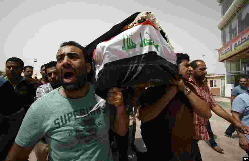 Iraqi men carry a coffin in the holy Iraqi city of Najaf on July 3 during a funeral procession for the victims of a suicide bombing that ripped through Baghdad's busy shopping district of Karrada. (AFP/Haidar Hamdani)
