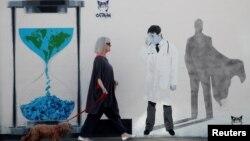 Žena prolazi pored grafita posvećenom lekarima koji su predstavljeni kao superheroji u borbi protiv korona virusa u Velikoj Britaniji