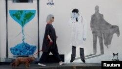 زنی در ویتستبل بریتانیا در حال عبور از برابر دیوارنگارهای درباره کرونا