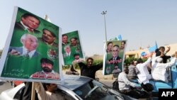 Supporters of Nawaz Sharif carry their party leaders' portraits during March 12 protest rally in Karachi