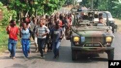 Французькі солдати проїжджають повз загін хуту, за 10 кілометрів від кордону з Заїром, 27 червня 1994 року