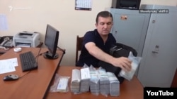 A screen-grab of Vachagan Ghazarian, a former bodyguard of Armenian ex-Prime Minister Serzh Sarkisian who was arrested after being stopped exiting a Yerevan bank on June 25 with more than $1 million in cash.