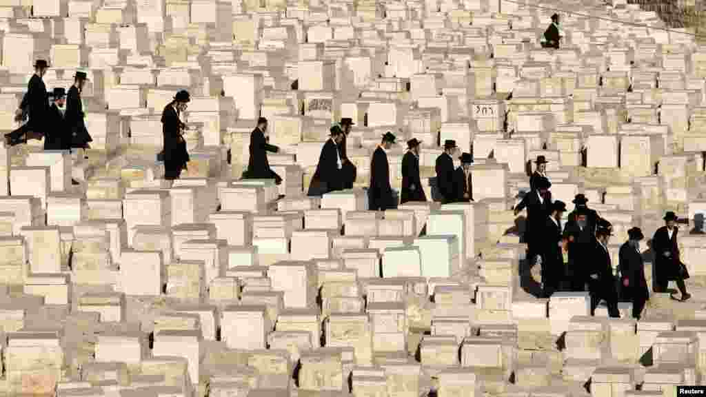 Ultra-Orthodox Jewish men walk between graves before the funeral of Rabbi Abraham Haim Roth, spiritual leader of the Shomrei Emunim Hasidic dynasty, in Jerusalem on August 23.  (REUTERS/Baz Ratner)